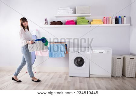 Young Woman Carrying Basket Full Of Dirty Clothes In Laundry Room