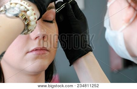 Cosmetologist Performs The Procedure Of Correction Eyebrow With Tweezers. Side View