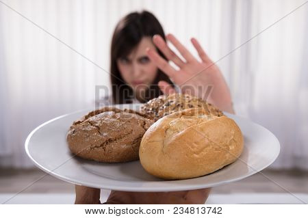 Woman Refusing Plate Of Bread And Cookies Offered By A Person