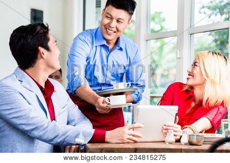 Friendly Asian waiter serving a stylish young couple coffee to accompany their meal in a restaurant with window background