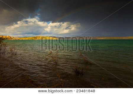 Rainbow and dark clouds over large lake
