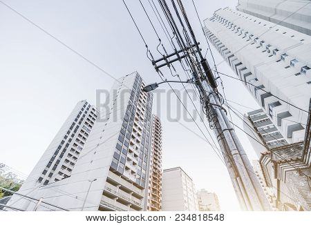 A Wide-angle Shot From The Bottom Of A Street Lantern With High-voltage Messy Wires Everywhere Conne