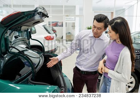 Asian Couple Discussing Small Trunk Of Car Automobile In Car Dealership