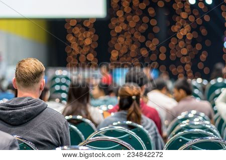 Rear View Of Audience In The Conference Hall Or Seminar Meeting Which Have Speakers On The Stage, Bu