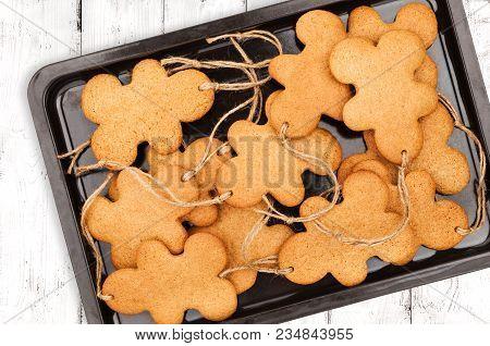 Baking Sheet With Gingerbread Men On Light Wooden Background Closeup