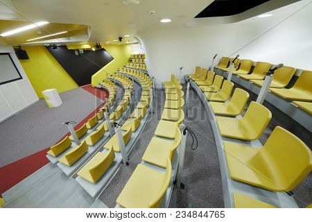 Auditorium with chairs and microphones, stand for speaker, screen on wall.