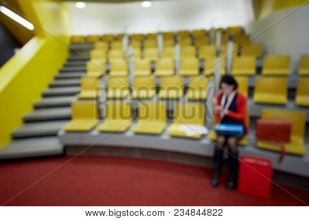 Woman sits in auditorium with yellow chairs, image out of focus.
