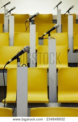 Microphones in holders on stands in auditorium with yellow chairs.