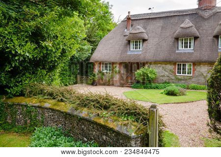 A typical traditional English country thatched house or cottage in rural Southern England UK