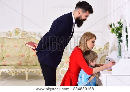 Parents Enjoying Parenthood, Teaching Child To Write. Home Schooling Concept. Father Peeking, While