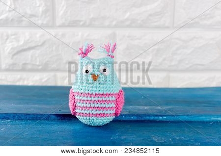 Cute Handmade Light Blue Knitted Owl Toy On A Brick Wall Background, Copy Spase
