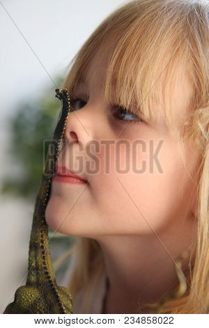 Portrait Of Cute Young  Girl With Blond  Hair Playing With Rubber Dinosaur