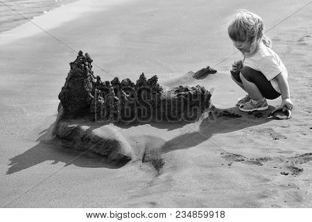 Cute Baby Boy With Blond Hair Ponytail In Blue Tshirt And Shorts Builds Sandcastle With Shovel On Se