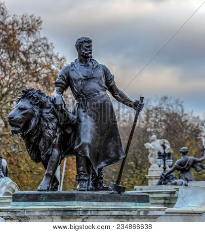 London, Uk - November 29, 2017: One Of Four Bronze Statues Around The Queen Victoria Memorial In Fro