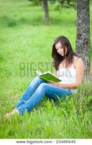 Outdoor Portrait Of A Cute Reading Teen