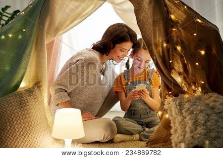 family, hygge and technology concept - happy mother and little daughter with smartphone in kids tent at night at home