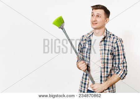 Young Tired Upset Housekeeper Man In Checkered Shirt Holding And Sweeping With Green Broom Isolated
