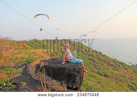 A Bald Man Sits On A Cliff Of A Mountain And Looks Out Into The Distance, Beyond The Horizon. Agains