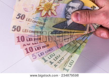 Мan Counts Romanian Banknotes On A White Background