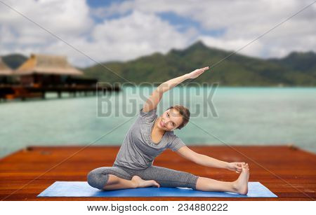 fitness, sport, people and healthy lifestyle concept - happy woman making yoga and stretching on wooden pier over island beach and bungalow background
