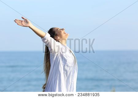 Side View Portrait Of A Satisfied Woman Breathing Fresh Air On The Beach