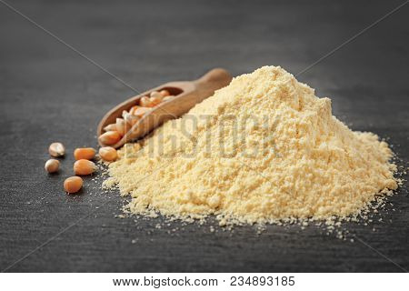 Pile Of Corn Flour And Scoop With Kernels On Table