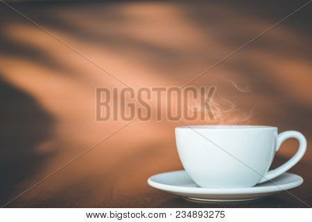 Close Up White Coffee Cup On Wooden Table Or Counter In Coffee Shop And Blur Light Bokeh Background