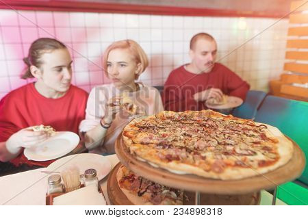 A Delicious Large Pizza On The Background Of People. A Group Of Young People Sits In A Cozy Pizzeria