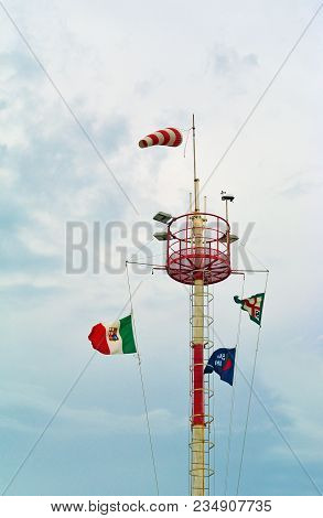 Windsock Tower At Windy Day. White And Red Conical Textile Tube, Color Flags, Cloudy Sky On Backgrou