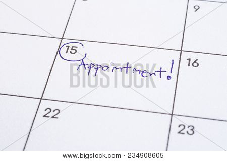 Closeup On Calendar Page, Focus On Blue Handwriting The Wordappointment Written On Timetable Date 1