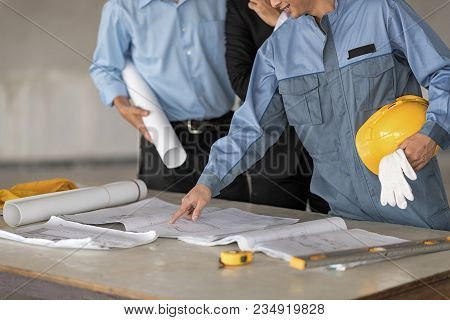 Engineer Is Pointing To Blueprint On The Table.hold Yellow Helmet On Left Hand. Blur Background Are
