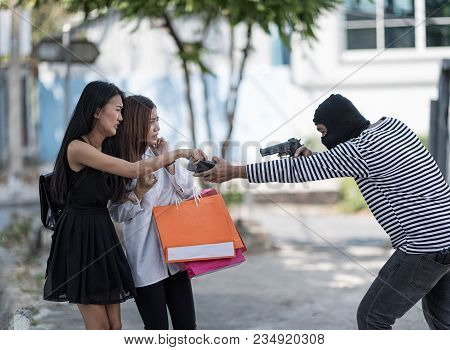 A  Masked Robber Is Robbing And  Aim A Gun At Two Shopping Women. They Are So Scared. Women Are Send