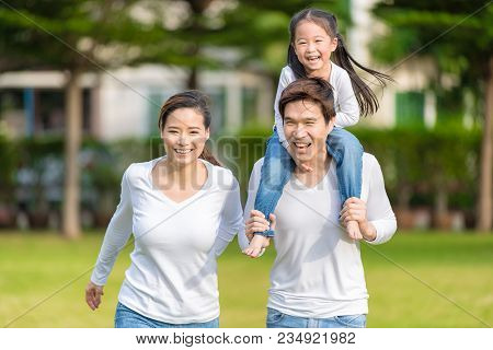 Cute Asian Girl On Neck Parents Big Happy Laughing And Run Around Together. Happy Family Piggybackin