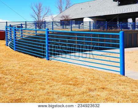 Tall Blue Metal Or Steel Fence By A Grass Area