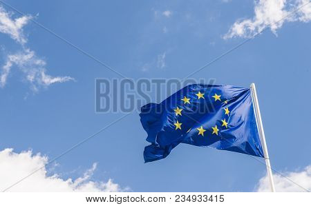 European Union Eu Flag Against A Blue Sky. Soon There Will Be One Less Star Since The Uk Voted To Le