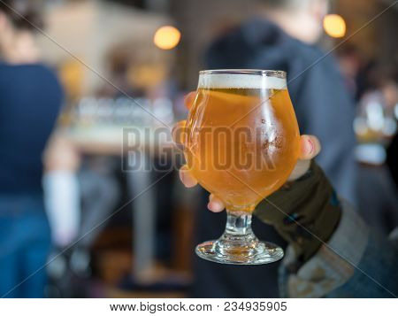 Close Shot Of A Hand Holding Light Beer Snifter (ipa) In Bar/brewery