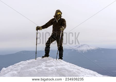 Mountaineer In A Windproof Mask And Glasses Reached The Snow Top Of The Mountain