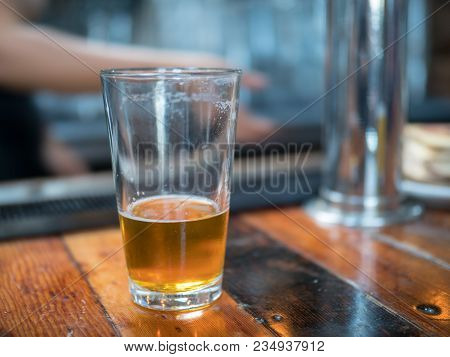 Almost Empty Pint Glass Of Beer Sitting On Wooden Bar For Last Call