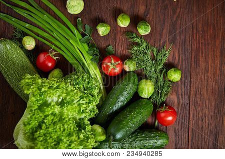 Vegetarian Still Life Of Fresh Vegetables On Wooden Plate Over Rustic Background, Close-up, Flat Lay