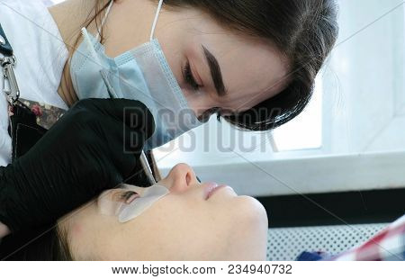 Beautician Separates The Lashes With A Needle And Bends Them Into Curlers. Lash Lamination. Closeup