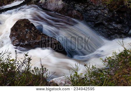 Idyllic waterfall scenery from hiking and recreation in wild highland nature.