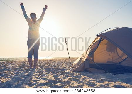 Joyful Woman Traveler, With Open Arms, Standing Next To Tent On The Seaside And Admiring Setting Sun