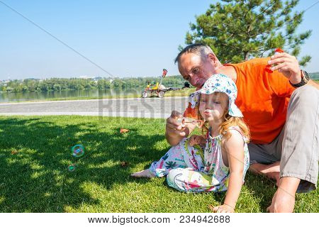 Happy Father And A His Cute Small Daughter Enthusiastically Inflate Soap Bubbles