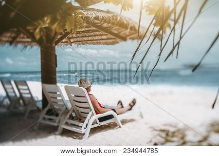 True Tilt-shift Shot An Elderly Man Relaxing Under The Sunshade On The Resort Daybed Located On The