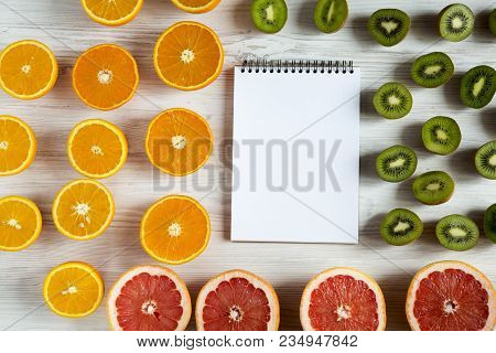 Flat Lay Top View Notebook With Sliced Kiwi, Orange, Grapefruit And Mandarin On Light Background. Su