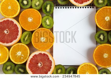 Flat Lay Top View Notebook With Sliced Kiwi, Orange, Grapefruit And Mandarin On Light Wooden Backgro