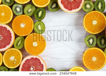 Flat Lay. Top View. Copy Space With Sliced Kiwi, Orange, Grapefruit And Mandarin On Light Wooden Bac