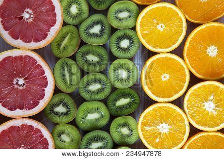 Flat Lay. Top View. Sliced Tropical Fruits: Kiwi, Orange, Grapefruit And Mandarin On Light Wooden Ba