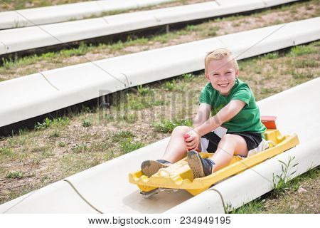 Cute smiling young boy riding downhill on an alpine coaster ride outdoors on a summers day. Happy and having fun on a thrilling theme park ride