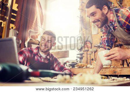 profession, carpentry, technology, woodwork and people concept - two carpenters with laptop computer at workshop
